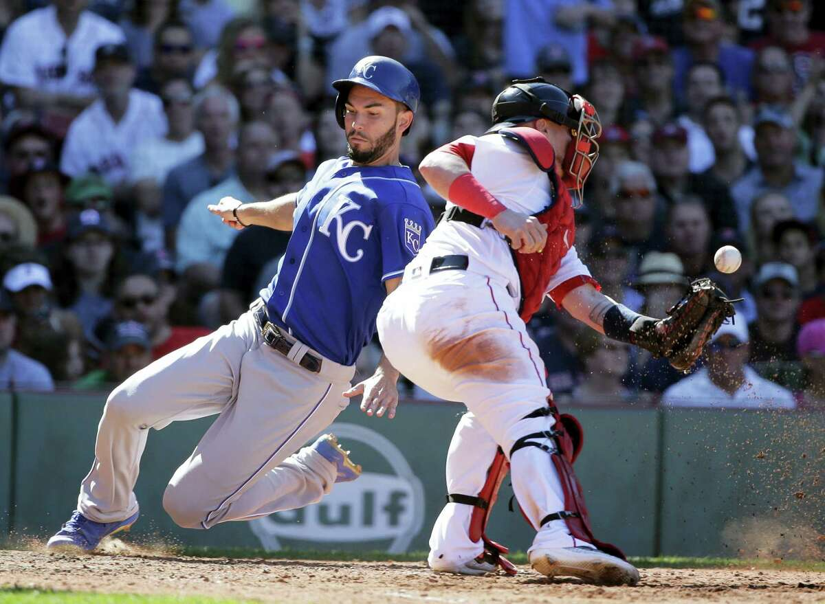 The Royals' Eric Hosmer, left, scores as Red Sox catcher Christian Vazquez tries to get his glove on the ball in the eighth inning Sunday in Boston.