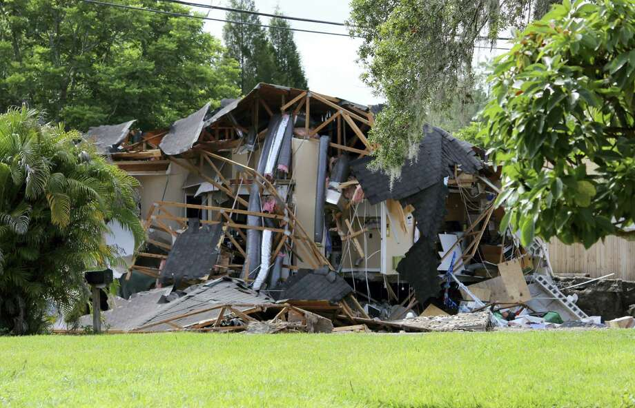 Debris is strewn about from a partially collapsed home in Land O' Lakes, Fla. on Friday, July 14, 2017.A sinkhole that started out the size of a small swimming pool and continued to grow has swallowed a home in Florida and severely damaged another. Photo: Alessandra Da Pra / Tampa Bay Times Via AP   / Tampa Bay Times