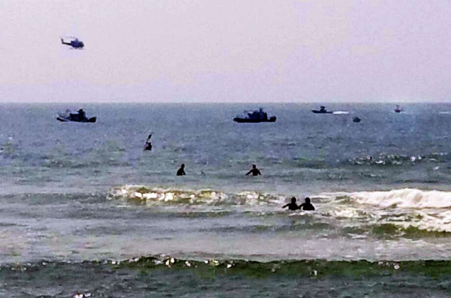 In this photo provided by ToniAnne Campasano Alvino, three rescue boats tow a helicopter that is almost entirely submerged, at far right, in the water off of Gilbo Beach, N.Y., on Long Island after the Robinson R 44 helicopter made an emergency ocean landing Wednesday, July 19, 2017. Shane McMahon, the son of World Wrestling Entertainment CEO Vince McMahon, was a passenger on the aircraft, and neither he, nor the pilot were hurt. The Federal Aviation Administration said the helicopter had taken off from Westchester County Airport in White Plains, N.Y. Photo: ToniAnne Campasano Alvino Via AP   / ToniAnne Campasano Alvino
