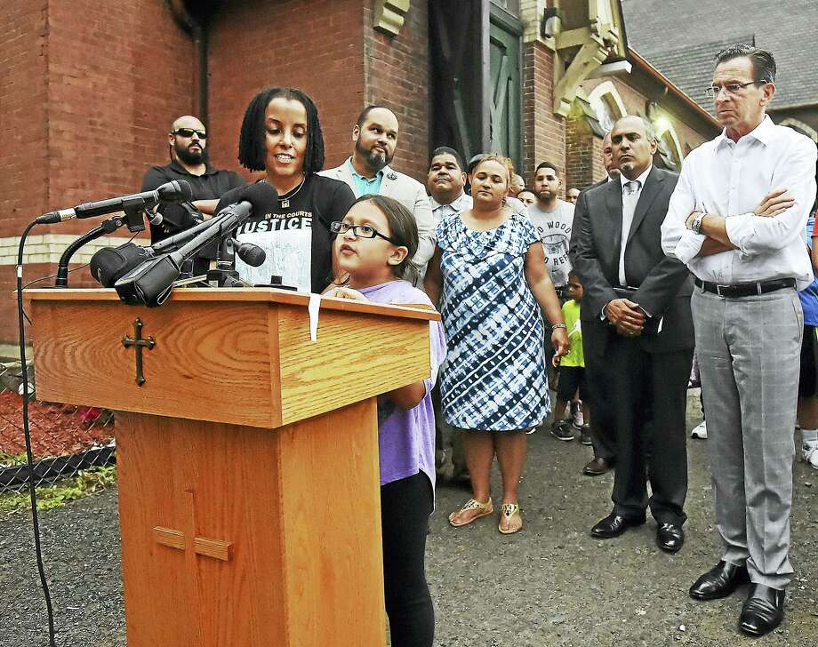 Activist Kica Matos stands at the side of Hayley Chavarria, as the 9-year-old daughter of Nury Chavarria speaks at a press conference Thursday in New Haven. Gov. Dannel P. Malloy is at right. Photo: Catherine Avalone / Hearst Connecticut Media   / Catherine Avalone/New Haven Register