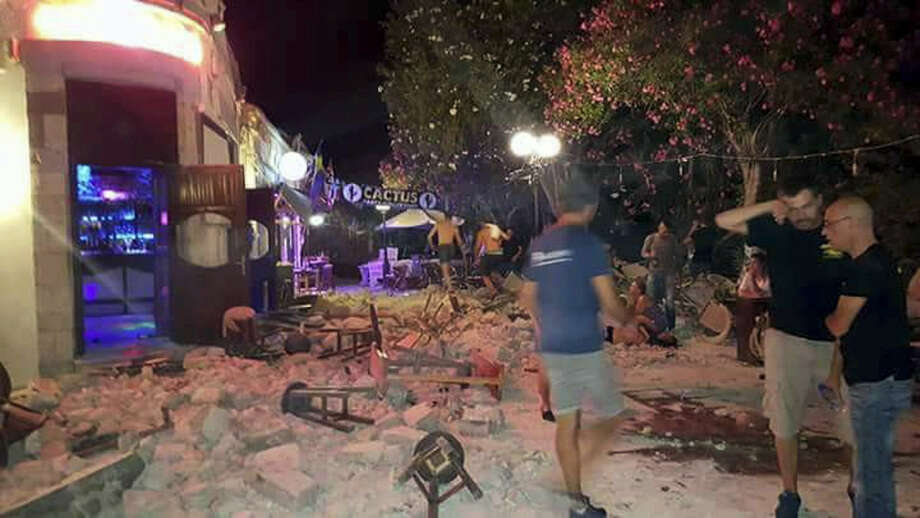 A man lies on the ground as other tourists stand outside a bar after an earthquake on the Greek island of Kos early Friday, July 21, 2017. A powerful earthquake struck Greek islands and Turkey's Aegean coast early Friday morning, damaging buildings and a port and killing at least two people, authorities said. Photo: Kostoday.gr Via AP   / KosToday