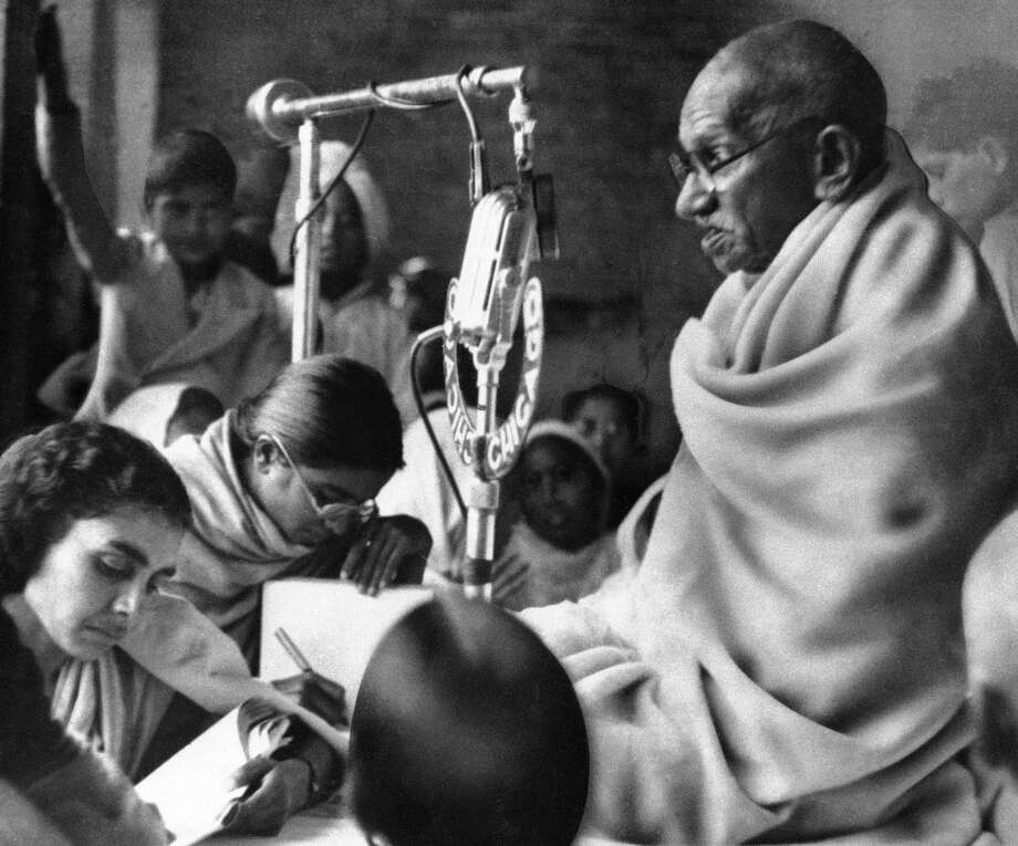 the associated press file photo  Mohandas K. Gandhi squats before a microphone in New Delhi, India, in 1948 to deliver prayer meeting discourse during second day of his fast to force communal peace in India. Photo: AP / AP