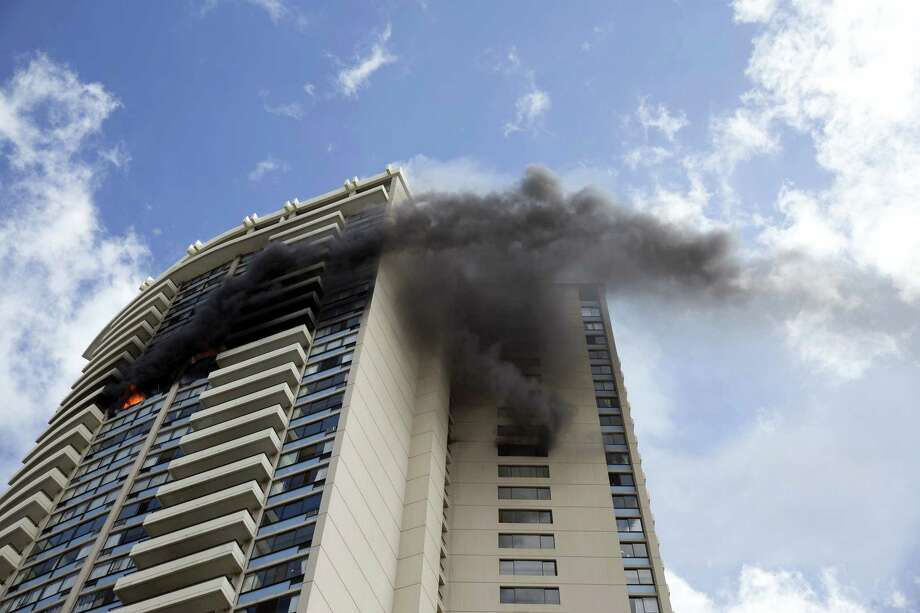 Smoke billows from the upper floors of the Marco Polo apartment complex, Friday, July 14, 2017, in Honolulu. Photo: AP Photo/Marco Garcia    / 2015