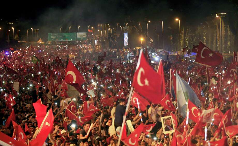 "Crowd cheer as Turkey's President Recep Tayyip Erdogan speaks at the July 15 Martyr's bridge on a ""National Unity March"" to commemorate the one year anniversary of the July 15, 2016, botched coup attempt, in Istanbul, Saturday, July 15, 2017. Turkey commemorates the first anniversary of the July 15 failed military attempt to overthrow president Erdogan, with a series of events honoring some 250 people, who were killed across Turkey while trying to oppose coup-plotters. Photo: AP Photo/Lefteris Pitarakis    / Copyright 2017 The Associated Press. All rights reserved."