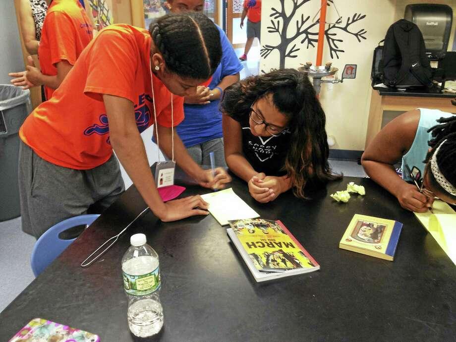LEAP Junior Counselor Elexis Eden looks over Michelle Fajardo's, 12, writing assignment. Photo: Brian Zahn / Hearst Connecticut Media
