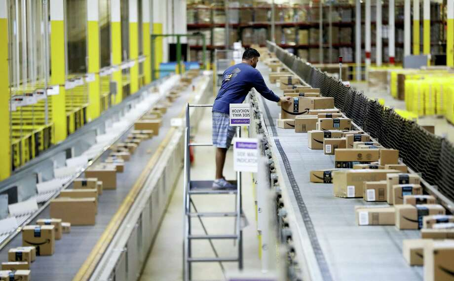 In this Aug. 1, 2017 photo, an Amazon employee makes sure a box riding on a belt is not sticking out at the Amazon Fulfillment center in Robbinsville Township, N.J. Amazon is holding a giant job fair Wednesday, Aug. 2, and plans to make thousands of job offers on the spot at nearly a dozen U.S. warehouses. Photo: AP Photo — Julio Cortez   / Copyright 2017 The Associated Press. All rights reserved.