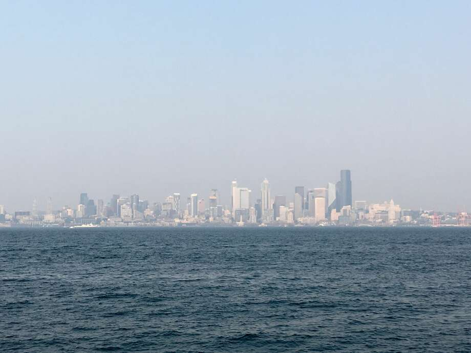 Downtown Seattle sits under a thick layer of smoke from British Columbia wildfires, as seen from Alki, Wednesday, Aug. 2, 2017. Photo: DANIEL DEMAY