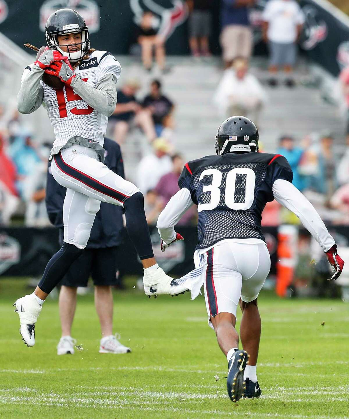 Texans cornerback Kevin Johnson, right, can do little but watch as wide receiver Will Fuller makes a catch in training camp. But by breaking his collarbone Wednesday, Fuller will be doing the watching for the next two to three months.
