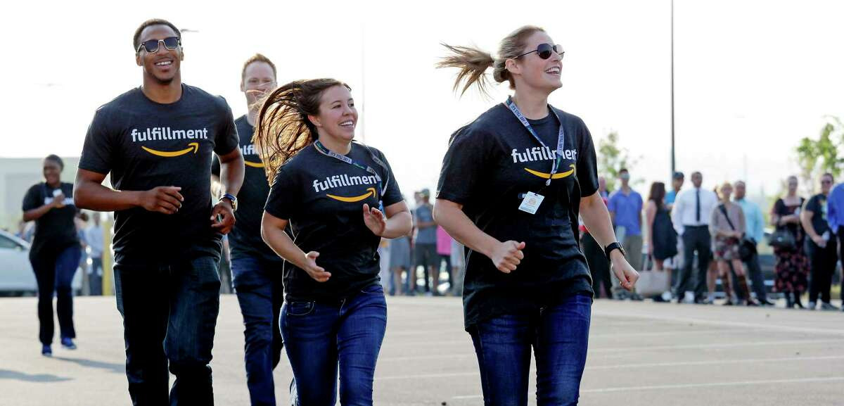 Amazon workers run past a line of applicants waiting to enter a job fair after greeting them with high-fives, Wednesday, Aug. 2, 2017, at an Amazon fulfillment center, in Kent, Wash. Amazon plans to make thousands of job offers on the spot at nearly a dozen U.S. warehouses during the recruiting event. (AP Photo/Elaine Thompson)