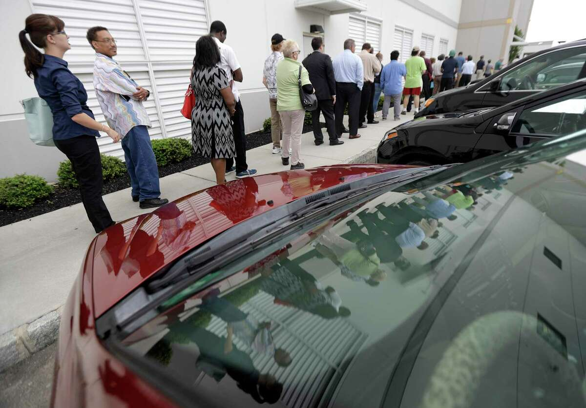 Job candidates stand in line outside the Amazon fulfillment center in Robbinsville, N.J., during a job fair, Wednesday, Aug. 2, 2017. Amazon plans to make thousands of job offers on the spot at nearly a dozen U.S. warehouses. (AP Photo/Julio Cortez)