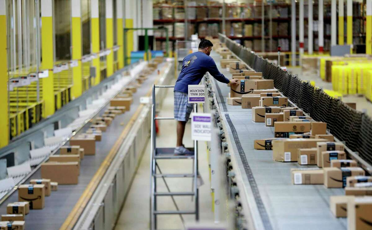 In this Tuesday, Aug. 1, 2017, photo, an Amazon employee makes sure a box riding on a belt is not sticking out at the Amazon Fulfillment center in Robbinsville Township, N.J. Amazon is holding a giant job fair Wednesday, Aug. 2, and plans to make thousands of job offers on the spot at nearly a dozen U.S. warehouses. (AP Photo/Julio Cortez)