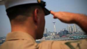 The Space Needle is visible as sailors and marines man the rails aboard the USS Anchorage during the Seafair Parade of Ships on Wednesday, August 2, 2017 on Puget Sound and along the Seattle waterfront.