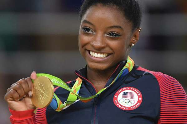 (FILES) This file photo taken on August 16, 2016 shows US gymnast Simone Biles celebrating on the podium of the women's floor event final of the Artistic Gymnastics at the Olympic Arena during the Rio 2016 Olympic Games in Rio de Janeiro. Biles on December 26, 2016 was named the Associated Press Female Athlete of the Year. / AFP PHOTO / Toshifumi KITAMURATOSHIFUMI KITAMURA/AFP/Getty Images