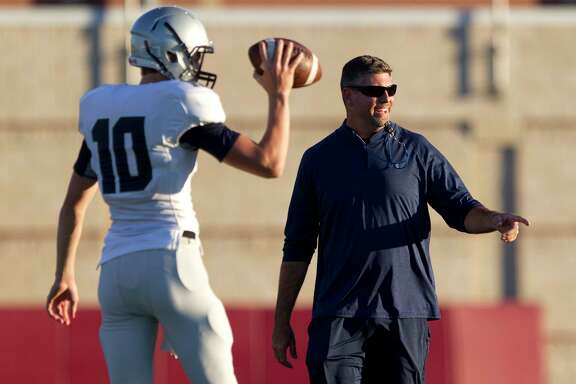 College Park head coach Lonnie Madison jokes alongside quarterback Max Bowman during a high school spring football game at Woodforest Bank Stadium, Wednesday, May 24, 2017, in Shenandoah.