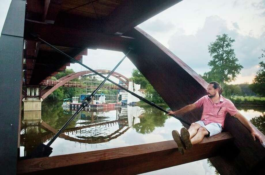 Paul Schuitema of Grand Rapids sits on a support beam underneath the Tridge while visiting the area on Tuesday. Work on the structure continues in the background.(Katy Kildee/kkildee@mdn.net)