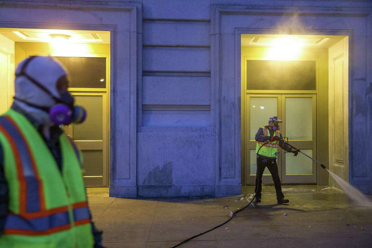 From left: Bernard Sices and Michael Chan with S.F. Public Works clean the sidewalk of human waste and trash outside the Bill Graham Civic Auditorium on Thursday, July 27, 2017.