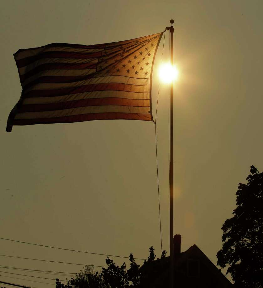 The evening sun shines through a U.S. flag flying in the wind against a sky made hazy with smoke from wildfires, Wednesday, Aug. 2, 2017, in Tacoma, Wash. The National Weather Service issued an excessive heat warning for western Washington and Oregon Wednesday and said the highs in Seattle on Thursday could hit 95 (35 Celsius) while Portland could reach 105 (40.5 Celsius). Photo: Ted S. Warren, AP / Copyright 2017 The Associated Press. All rights reserved.