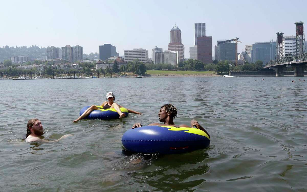 People cool off in the Willamette River with the downtown skyline visible in the background in Portland, Ore., Wednesday, Aug. 2, 2017. Scorching temperatures are predicted for the Northwest Wednesday and Thursday, with forecasters saying Seattle and Portland could top triple digits and break records.