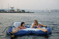 Floaters enjoy the cool water after a hot day at Lake Union Park on Wednesday, Aug. 2, 2017.