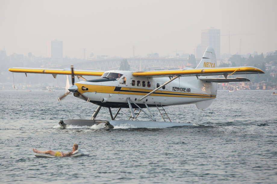 A Kenmore seaplane passes by a beachgoer in a raft off Lake Union Park on Wednesday, Aug. 2, 2017. The company announced on Wednesday that it will soon begin daily service to Vancouver, British Columbia. Photo: GRANT HINDSLEY, SEATTLEPI.COM / SEATTLEPI.COM