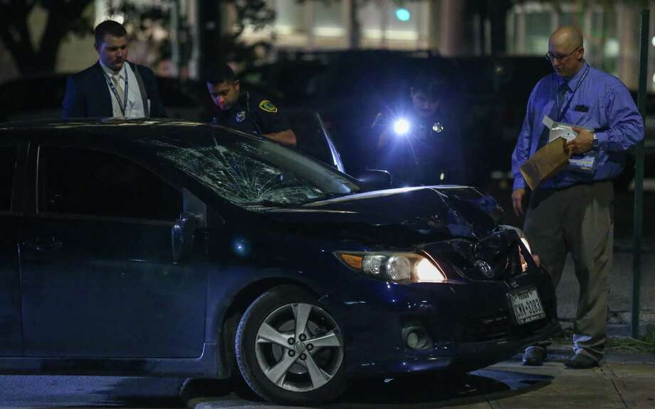 Houston Police officers investigate the scene where a vehicle with three occupants drove into a crowd outside the Spire Night Club, striking at least one person, on the intersection of Travis and Jefferson streets Thursday, Aug., 3, 2017, in Houston. The three men inside the vehicle were then shot at as they were trying to leave the scene, according to police. Photo: Godofredo A. Vasquez / Houston Chronicle