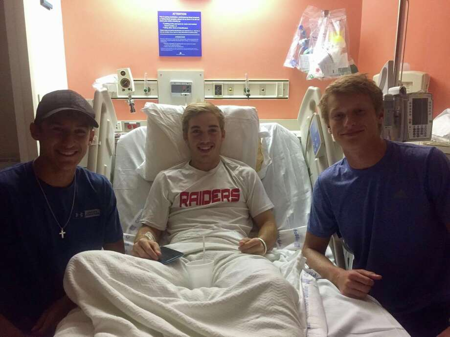 Friends Tyler Leblanc (left) and Caleb Kerr (right) visit with Braden Carter at Texas Children's Hospital in Houston. Photo: Tarin Starnes