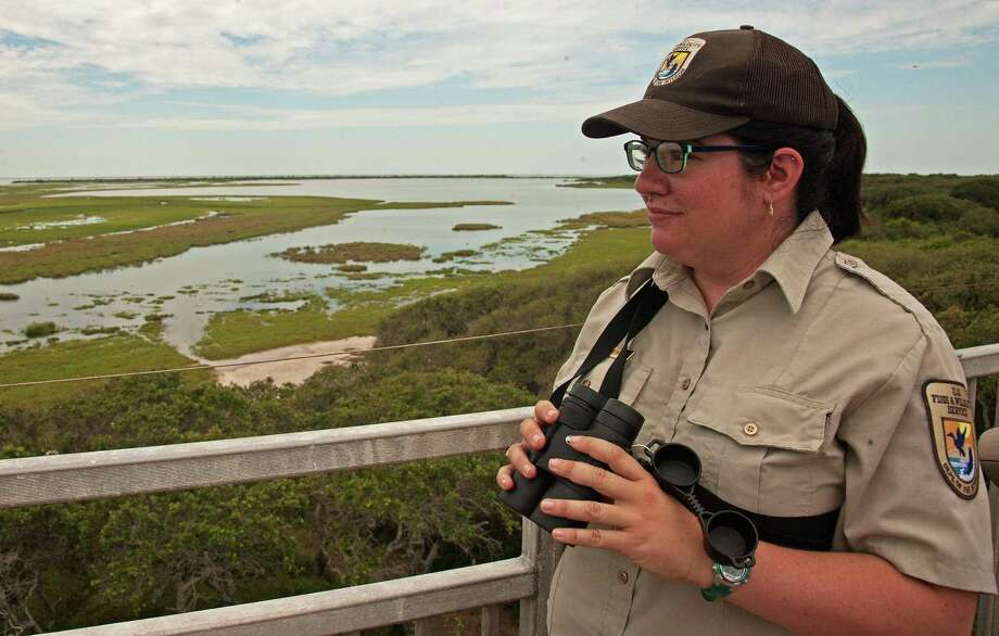 Atop the 40-foot-tall observation tower, visitor services manager Laura Bonneau takes in the view of Mustang Lake in background, San Antonio Bay and the wetlands around them that provide food for whooping cranes, shore birds and waterfowl. Photo: John Goodspeed / For The Express-News