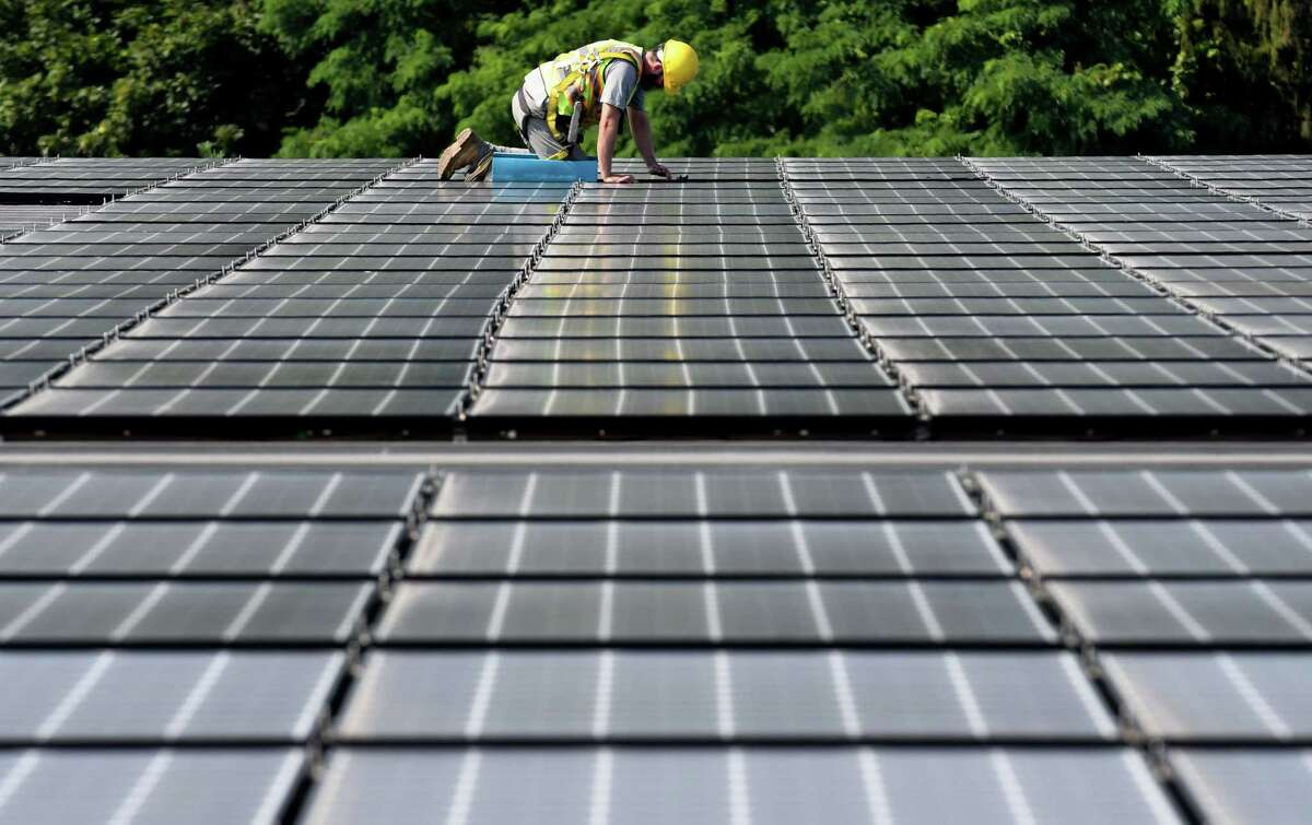 Panels for a solar array are installed on the roof of Dimension Fabricators on Thursday, Aug. 3, 2017, in Glenville, N.Y. (Will Waldron/Times Union)