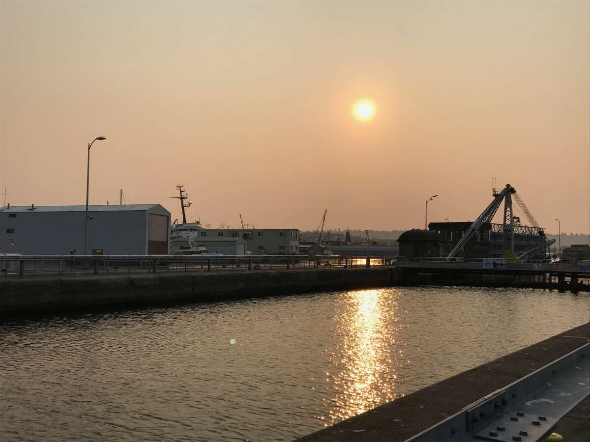 A layer of wildfire smoke obscured the sun and altered its color Thursday morning, as seen in this photo taken at the Ballard Locks. Air quality was unhealthy and smoke was expected to remain in the area for at least another day.
