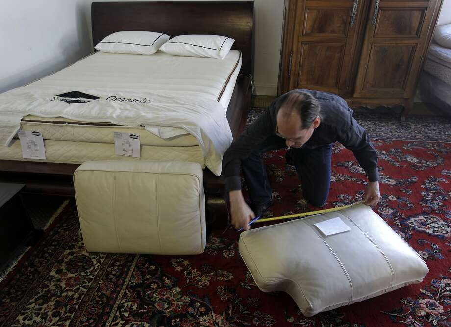 Alan Buhtz of Foam Order measures sofa cushions in 2014 for customers wanting new cushions without flame retardants. Photo: Paul Chinn, The Chronicle