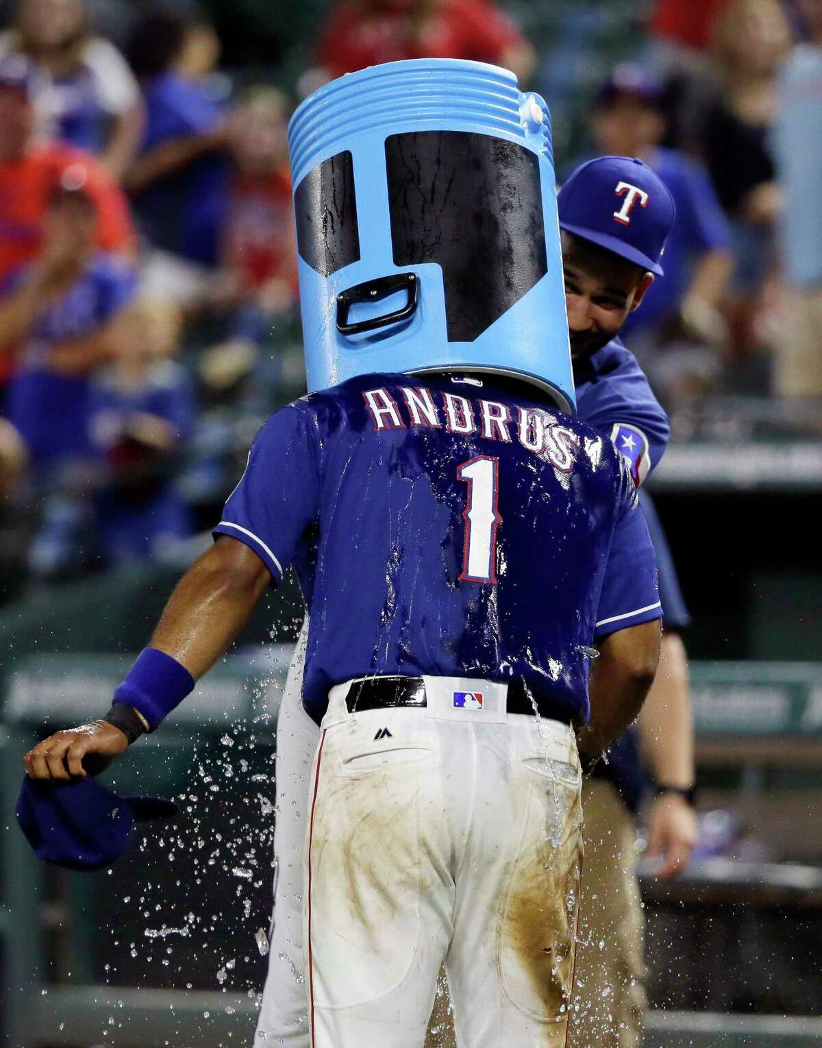 Texas Rangers' Elvis Andrus has a water cooler placed over his head after being doused by Nomar Mazara, rear, following thet team's 5-1 win over the Seattle Mariners in a baseball game Wednesday, Aug. 2, 2017, in Arlington, Texas. (AP Photo/Tony Gutierrez) ORG XMIT: ARL119 ORG XMIT: MER2017080300090390