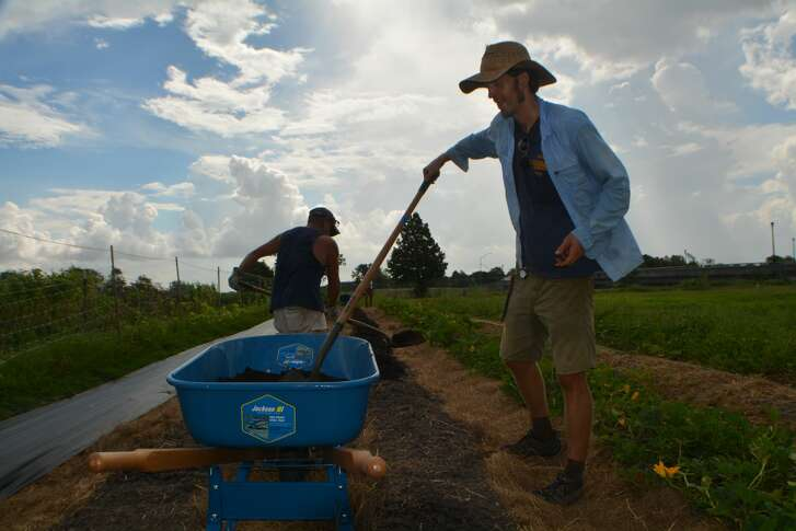 SUNNYSIDE - Justin Myers and military veteran Ronnie Wright lay soil, prepping the ground for the farm's fall production. (Aug.2, 2017)