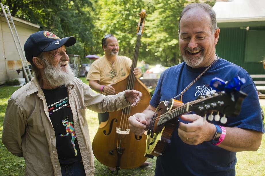 William Smith of Edenville, left, chats with Tom Galbraith of Ohio, right, and Gil Evans of Ohio, center, as they rehearse before performing with the rest of the Fossil Creek Band during the Salt River Bluegrass Festival on Friday, July 28 in Oil City. Photo: (Katy Kildee/kkildee@mdn.net)