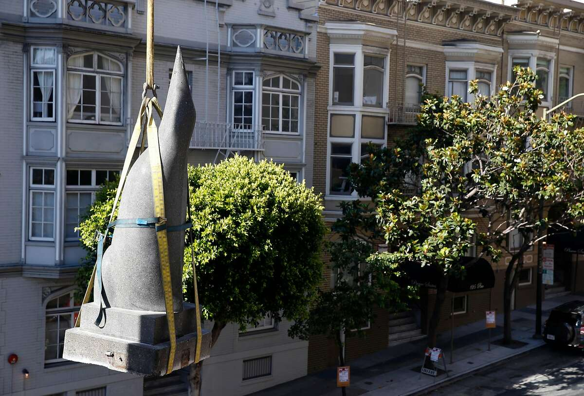 A crane lowers a penguin sculpture by artist Beniamino Bufano from its perch above Pine and Powell streets where it was installed in the back corner of the Stanford Court Hotel in San Francisco, Calif. on Saturday, July 22, 2017. The penguin will be restored and reinstalled at the main entrance of the hotel, which is undergoing a renovation, on California Street.