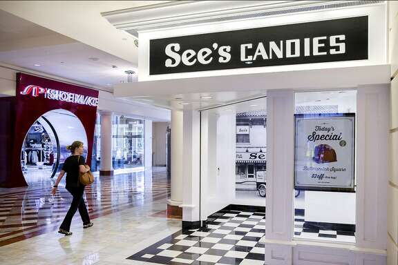 A woman walks past See's Candies inside the Stonestown Galleria on Tuesday, Aug. 1, 2017, in San Francisco, Calif.