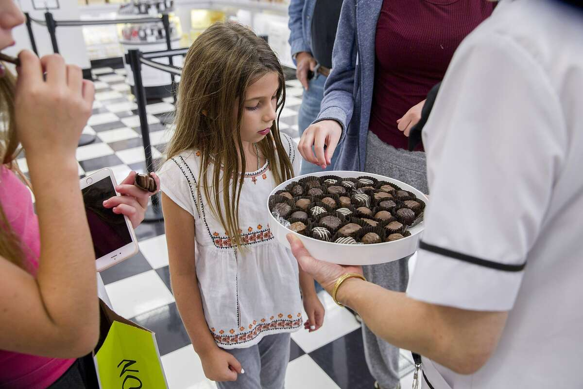 India Sanor, 8, checks out the chocolate sample from Jeannie Jew at See's Candies inside the Stonestown Galleria.