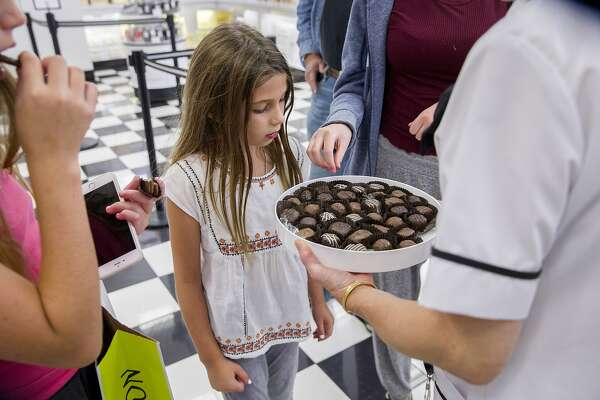 India Sanor, 8, checks out the chocolate sample from Jeannie Jew at See's Candies inside the Stonestown Galleria on Tuesday, Aug. 1, 2017, in San Francisco, Calif.