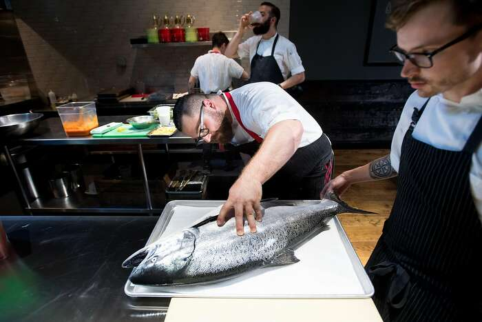 Lazy Bear chef de cuisine Chris Johnson examines a king salmon on Wednesday, Aug. 2, 2017, in San Francisco. AT right is sous chef Matt Hanley.