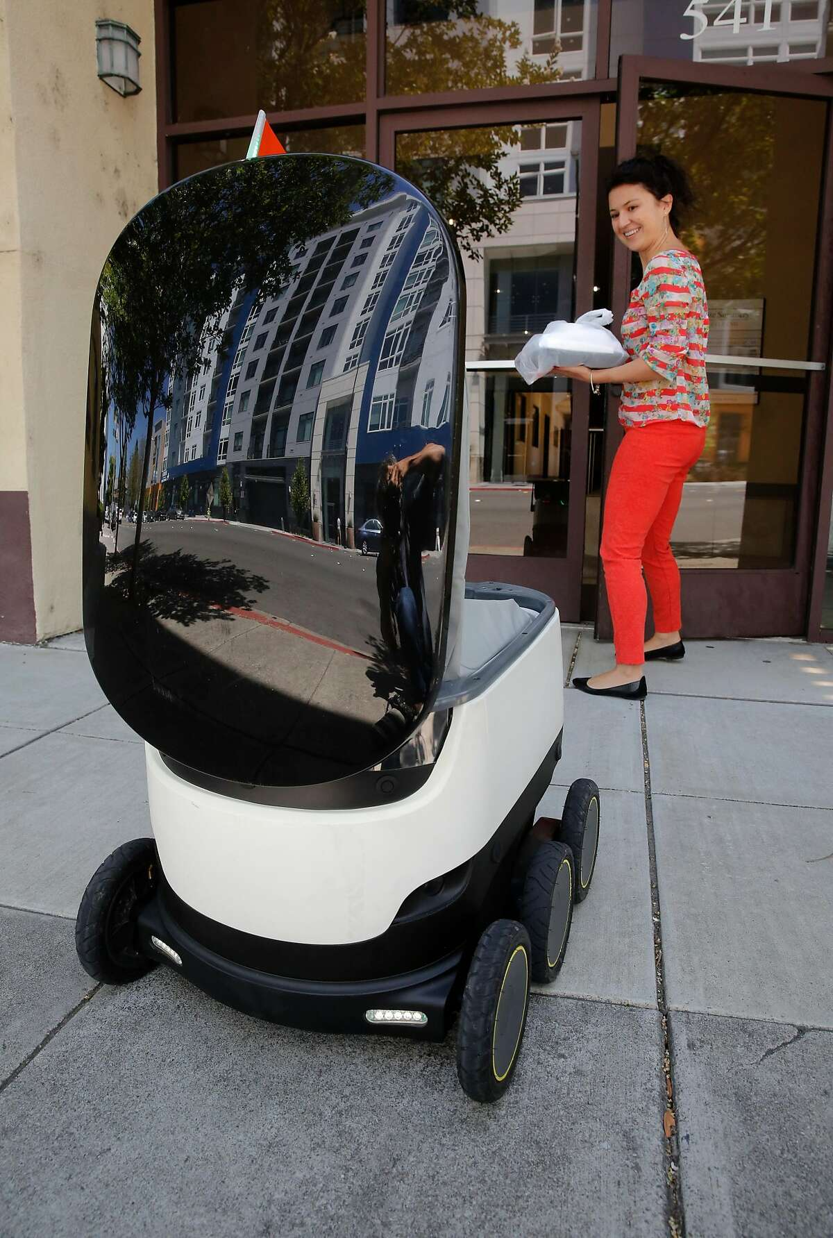 Elena Savateyev, with White Summers Caffee & James, an IP technologies law firm, picks up a food delivery from one of the robots operated by Starship Technologies in downtown Redwood City, Ca., on Tuesday July 18, 2017.