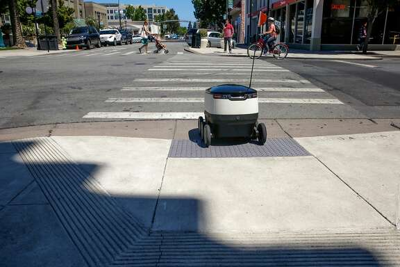 One of the robots operated by Starship Technologies navigates the streets of downtown Redwood City, Ca. during a delivery on Tuesday July 18, 2017.