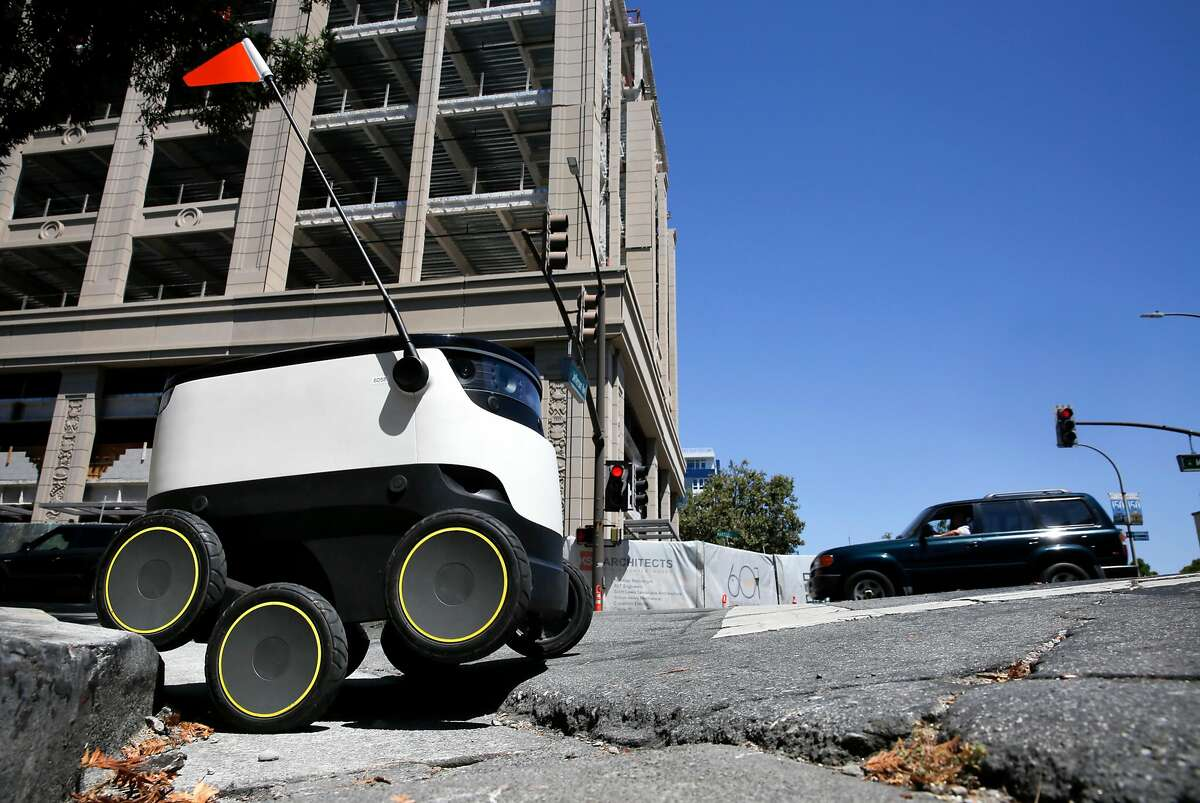 A Starship Technologies robot navigates streets in downtown Redwood City.