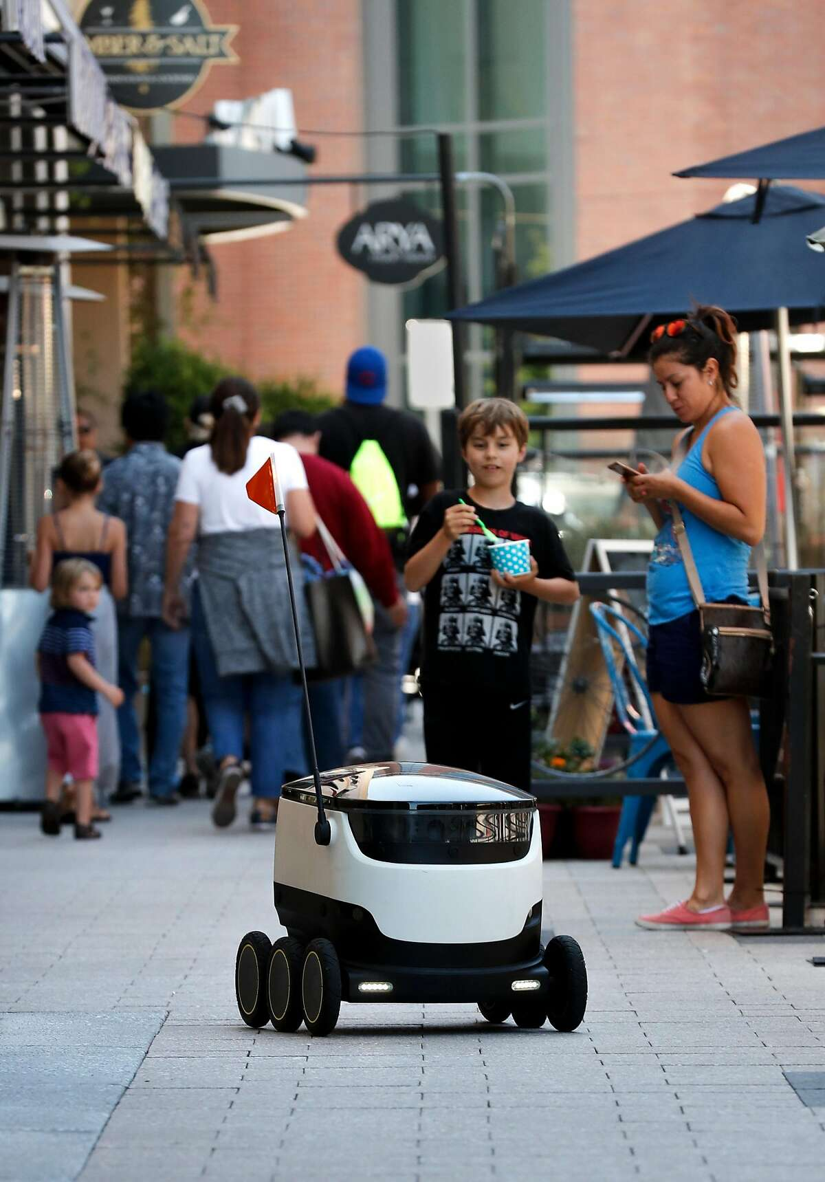 One of the robots operated by Starship Technologies navigates through downtown Redwood City, Ca. during a delivery on Tuesday July 18, 2017.