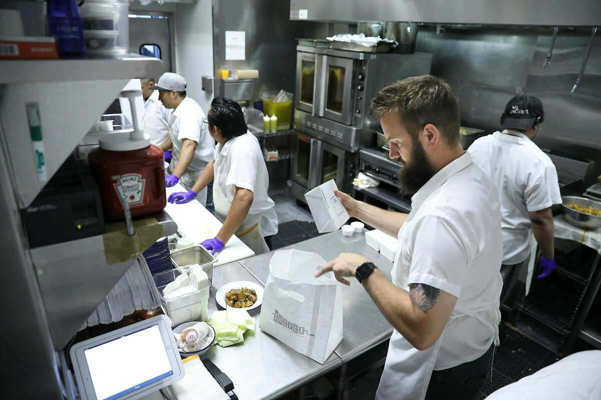 Souvla is a fast-casual restaurant at which 25% of its business is delivery. Ross Wunderlich, Kitchen Manager and the Expeditor at Souvla, preparing meals as seen in San Francisco, California on Tuesday, July 25, 2017.