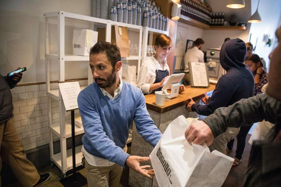 Christopher Tishlias, General Manager at Souvla, hands out takeout bags of prepared meals in San Francisco. Photo: Craig Lee, Special To The Chronicle