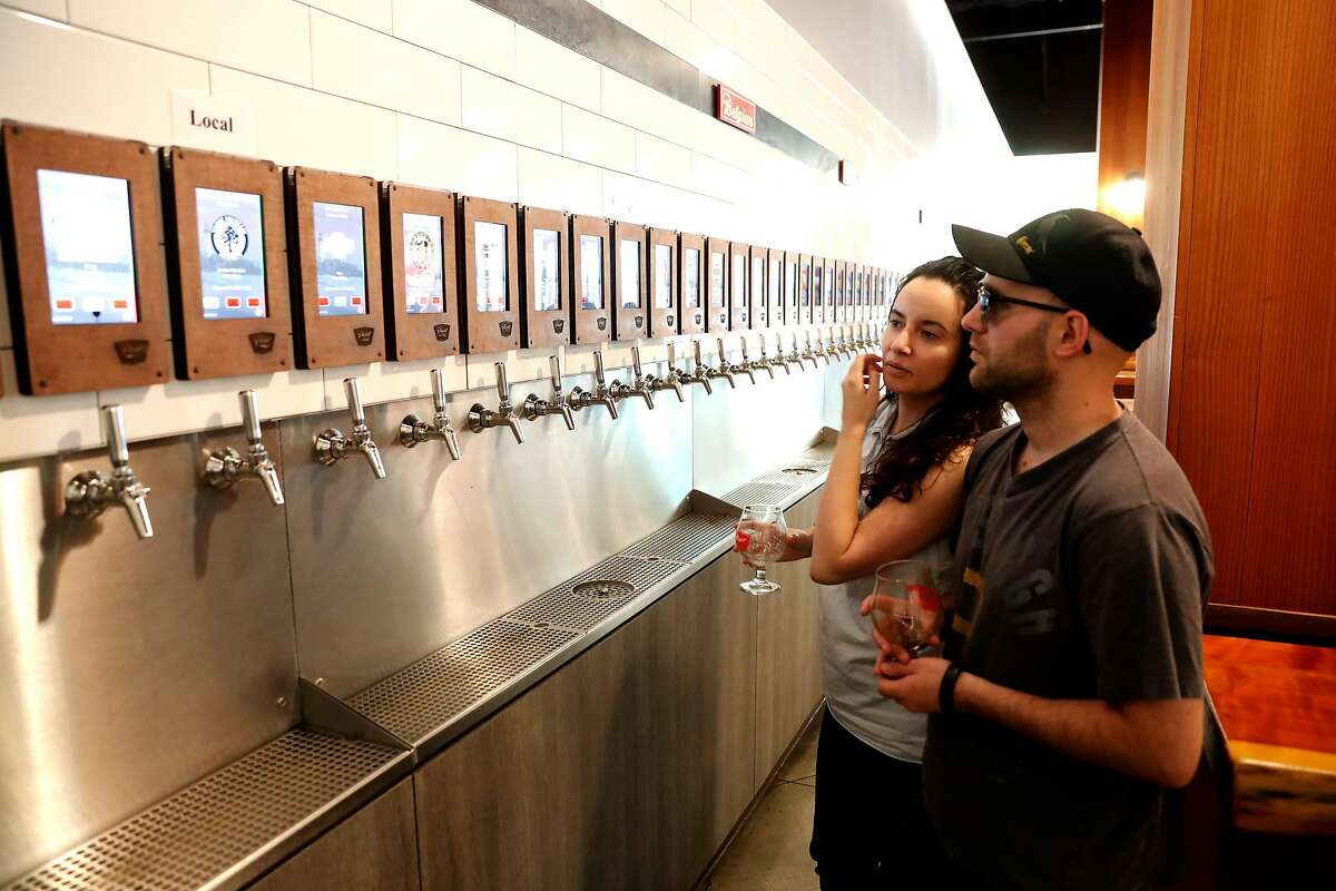 Mitchell and Jasmine Conley look over the selections of 70 beers on tap at Pour Taproom as seen on Thurs. July 27, 2017 in Santa Cruz, Ca.