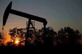 In this Feb. 19, 2015 photo, the sun sets behind an oil well in a field near El Tigre, a town within Venezuela's Hugo Chavez oil belt, formally known as the Orinoco Belt. President Nicolas Maduro, whose approval rating has plunged to around 25 percent, has no choice but to lean on state-fun oil company PDVSA to help Venezuela back on its feet and has been quietly trying to lure back foreign drillers. (AP Photo/Fernando Llano)