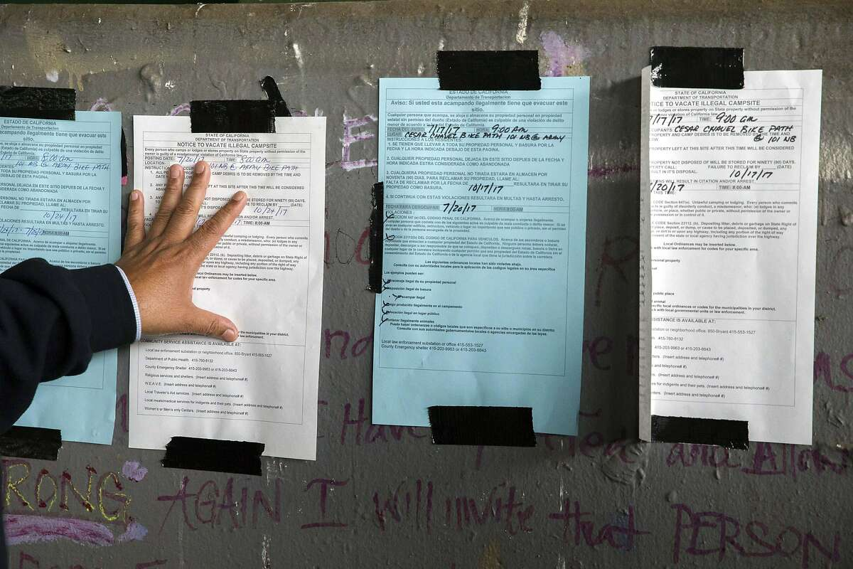 Public Works Director Mohammed Nuru looks at campsite notices to evict near Cesar Chavez Street and Potrero Avenue.
