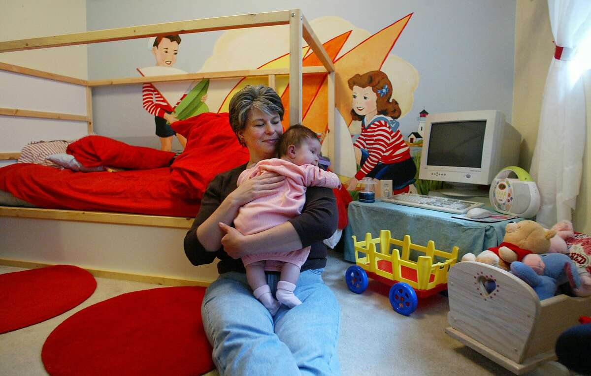 Andrea Riseden-Perry cradles her four month old daughter Genoa in her four-year old daughter Aspen's bedroom. Riesden-Perry knows that her breast milk likely contains chemical flame retardants called PBDEs. The chemicals, which cause neurological and developmental problems in experiments with baby mice, were detected in her mild after her first daughter was born. Because breast milk is the best food for babies, Riesden-Perry is continuing to nurse her second daughter, who was born in December. Riesden-Perry was careful to buy a non-toxic mattress for her daughter's bedroom. Paul Joseph Brown photo/Seattle P-I