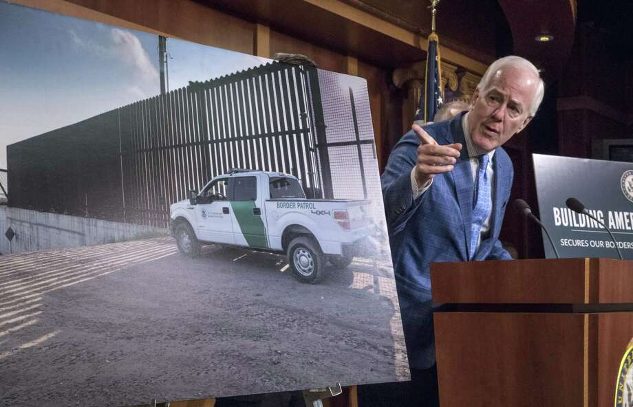 Senate Majority Whip John Cornyn of Texas, points to a poster with an image of barrier on the Texas-Mexico border as he talks to reporters about border security, Thursday, Aug. 3, 2017, on Capitol Hill Washington. (AP Photo/J. Scott Applewhite) Photo: J. Scott Applewhite, STF / Associated Press / Copyright 2017 The Associated Press. All rights reserved.
