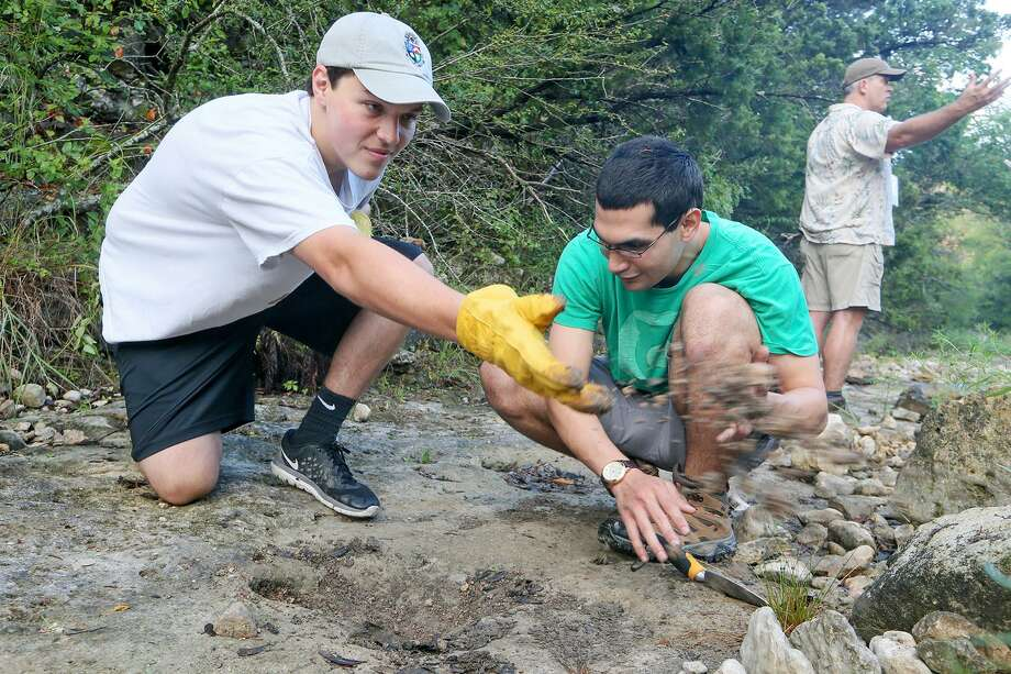 Callaway Metcalfe (left) and Richard Gonzalez clean debris from a theropod track. The tracks are found down the Joe Johnston Route. Photo: Marvin Pfeiffer /San Antonio Express-News / Express-News 2017